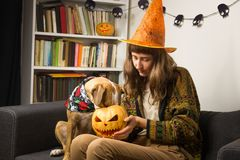 Girl in halloween hat sits with curious dog who sticks its nose stock photo