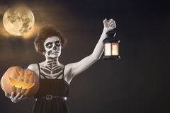 Girl with Halloween make up hold pumpkin and candlestick. Autumn. Girl with Halloween make up hold pumpkin and candlestick against a full moon. Autumn stock image
