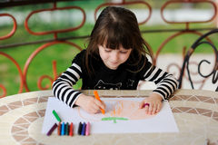 Girl in Halloween outfit draws pumkin Royalty Free Stock Photo