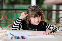 Girl in Halloween outfit draws pumkin Stock Image