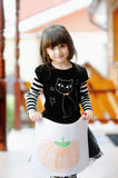 Girl in Halloween outfit shows her pumkin drawing. Adorable small gir with long hair in Halloween outfit shows her pumkin drawing outside royalty free stock photos
