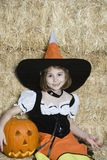 Girl In Halloween Outfit Sitting By Hay With Jack-O-Lantern. Portrait of a cute little Caucasian girl in Halloween outfit sitting by hay holding Jack-O-Lantern Stock Image