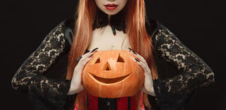 Girl with Halloween pumpkin on black background stock image