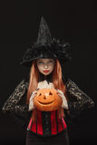 Girl with Halloween pumpkin on black background Stock Images