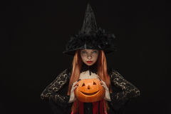 Girl with Halloween pumpkin on black background Royalty Free Stock Photography