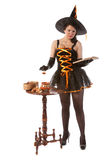 Girl in Halloween witch costume prepares a potion Royalty Free Stock Image