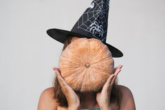Girl in Halloween witch hat with pumpkin Royalty Free Stock Images