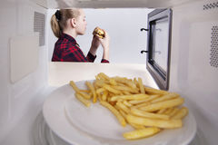 Girl with a hamburger in hands sitting at table. Warming up a quick meal in the microwave. View through oven Stock Image