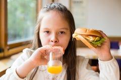Girl with hamburger and orange juice Royalty Free Stock Photos