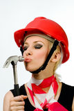 A girl with a hammer and a construction helmet royalty free stock image