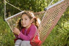 Girl in hammock. Little girl sitting in a hammock in backyard Stock Photography