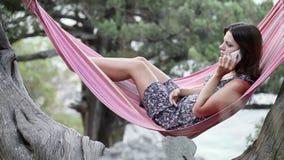Girl in hammock smartphone Stock Images