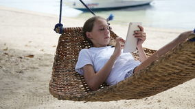 Girl in the hammock with the tablet on the beach stock video