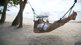Girl in the hammock with the tablet on the beach stock footage