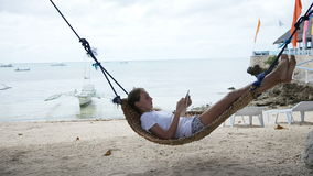Girl in the hammock with the tablet on the beach stock video footage