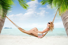 Girl in hammock. View of nice young lady swinging  in hummock on tropical beach Royalty Free Stock Photography
