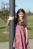 Girl with hand around light pole Stock Photography