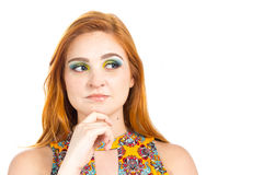 Girl with hand on chin looks to the side. Redheaded girl wearing Stock Image