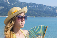 Girl with hand cooling fan at the beach. Summer vacation backgro Stock Photos