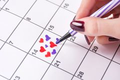 Girl hand drawing hearts in calendar with felt pen for Valentines day royalty free stock images