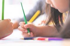 Girl hand drawing in kindergarten art classroom. Girl hand is drawing in kindergarten art classroom stock images