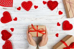 Girl hand give valentine gift box with a red heart inside on a white old wooden table. Valentine day.  Stock Images
