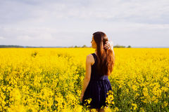 Girl with hand in hair on rapeseed meadow Royalty Free Stock Images
