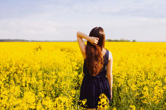Girl with hand in hair on rapeseed meadow Stock Photography