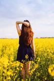 Girl with hand in hair on rapeseed meadow Stock Photos