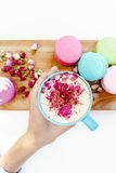 Girl hand hold a blue cup of morning aroma cappuccino. French macarons and roses petals on wood desk Stock Photography