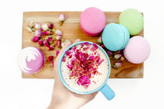 Girl hand hold a blue cup of morning cappuccino coffee. French macarons and roses petals on wood desk Stock Photo
