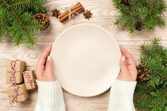 Girl hand hold Top view. Empty white plate on wooden background with christmas decoration. New Year concept royalty free stock images