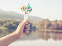 Girl hand holding coloful sweet. Girl hand holding colorful sweet with a vintage retro filter effect,summer season royalty free stock images