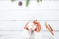 Girl hand holding cup of hot chocolate on white table Stock Image