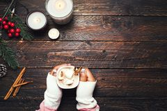 Girl hand holding cup of hot chocolate on white table with rustic decoration Royalty Free Stock Images