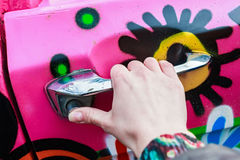Girl hand holding doorhandle of pink colorful car Royalty Free Stock Image