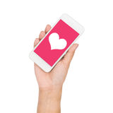 Girl hand holding mobile phone display heart on pink screen Stock Photo