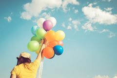 Girl hand holding multicolor balloons done with a retro instagram filter effect,. Concept of happy birth day in summer and wedding honeymoon party, Vintage Stock Photos