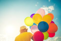 Girl hand holding multicolor balloons done with a retro instagram filter effect,. Concept of happy birth day in summer and wedding honeymoon party, Vintage Stock Image