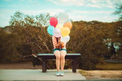 Girl hand holding multicolor balloons. Done with a retro instagram filter effect, concept of happy birth day in summer and wedding honeymoon party, Vintage Royalty Free Stock Photo