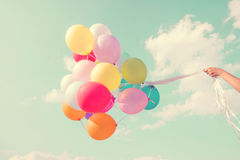 Girl hand holding multicolored balloons. Done with a retro vintage  filter effect, concept of happy birthday in summer and wedding honeymoon party Vintage color Stock Image