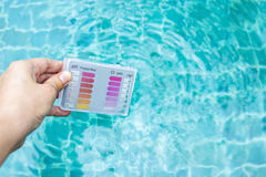 Girl hand holding water testing test kit dipping in swimming pool water Royalty Free Stock Photography