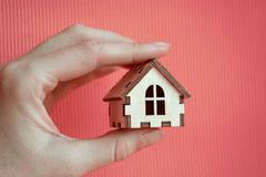 Girl hand holding wooden miniature toy house on the sunlight with pink background stock images