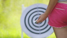 Girl in hand holds darts for darts on the nature. Closeup girl`s hand with darts for darts. Girl in hand holds darts for darts on the nature stock video footage