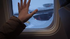 Girl hand on an illuminator of aircraft just before takeoff and fly away stock video