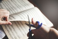 Girl hand music notes with scissors royalty free stock photography