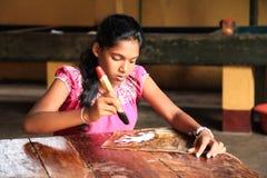 Girl hand painting fabric. Sri Lanka - January 3, 2017: Young girl hand painting fabric in a local Batik factory - store Royalty Free Stock Image