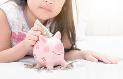 Girl hand put money to piggybank on bedroom Royalty Free Stock Images