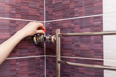 The girl hand regulates the water tap in the heated towel rail. The girl hand regulates the water tap in the heated towel rail Stock Image