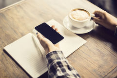 Girl  hand with smartphone, blank diary and cup of coffee Stock Photo